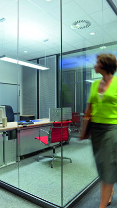 Woman is looking to the Philips light illuminating the private office of Audi