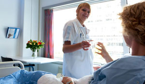 Nurse is offering a glass of water to a patient
